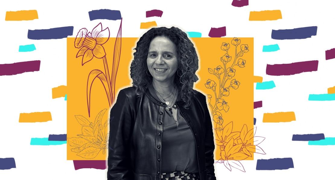 Foto em preto e branco da artista plástica Beatriz Milhazes. Ao fundo, silhuetas de flores aparecem em frente a um retângulo amarelo. Ao fundo branco, retângulos lilazes e azul-claros.