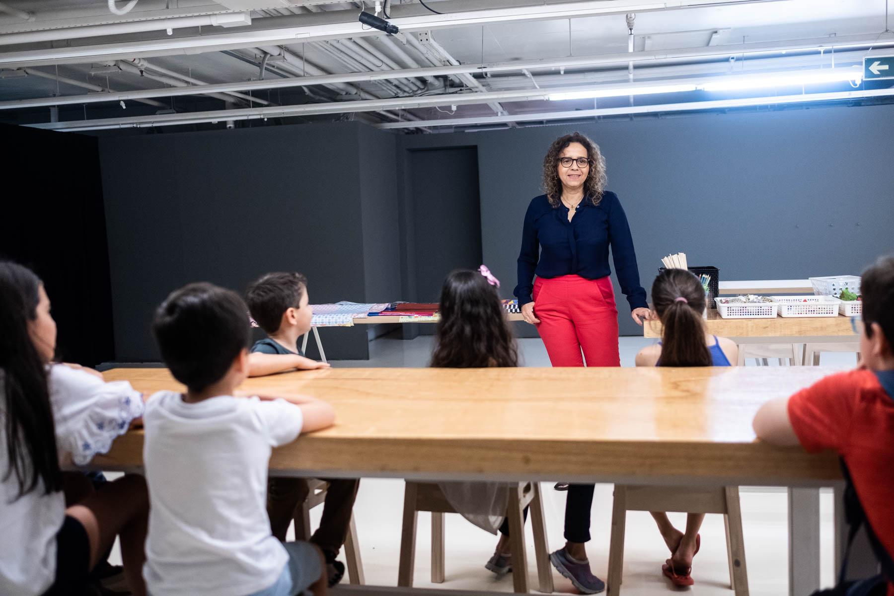 Crianças sentadas em bancos ao redor de uma bancada de madeira ouvem atentas as instruções da artista plástica Beatriz Milhazes