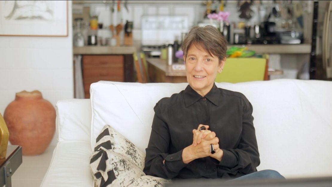 Astróloga sentada em um sofá branco explica as características do site Capitu