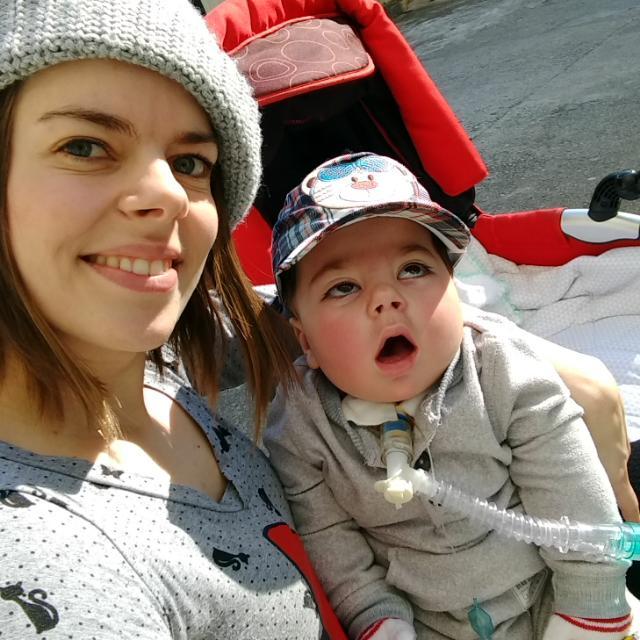 Mãe sorri para foto com o filho no colo