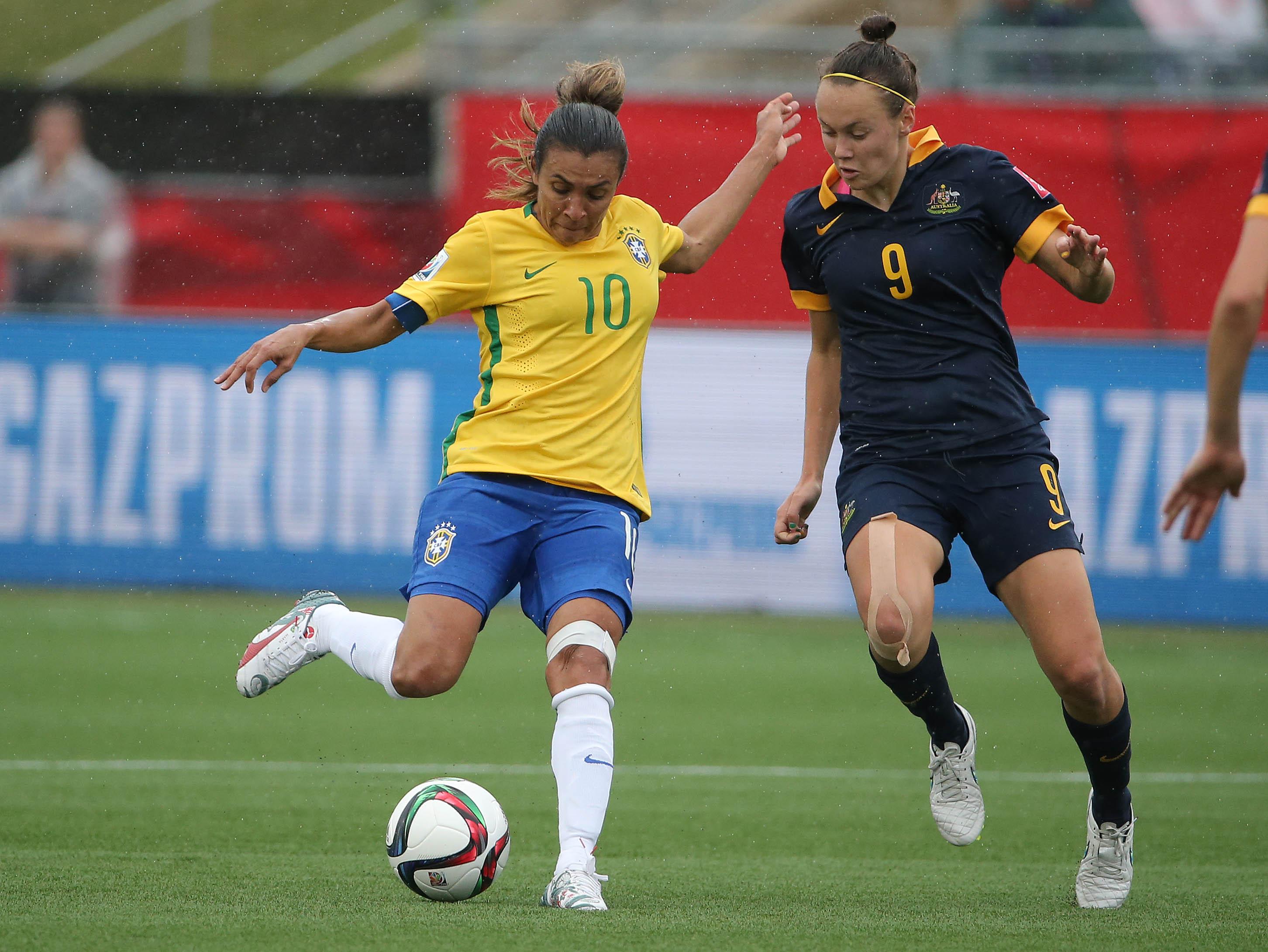 A atacante brasileira Marta chutando uma bola durante uma partida de futebol