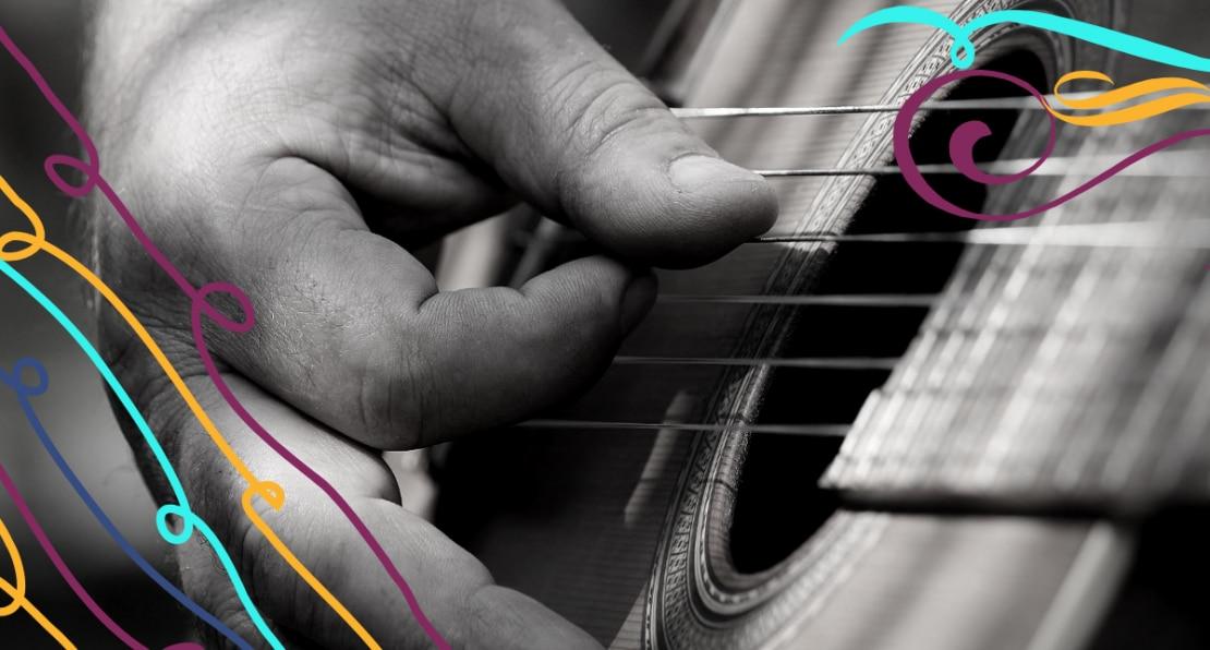 Mão dedilha cordas de um violão