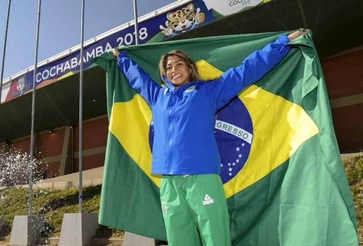Atleta Valéria Kumizaki segurando bandeira do Brasil