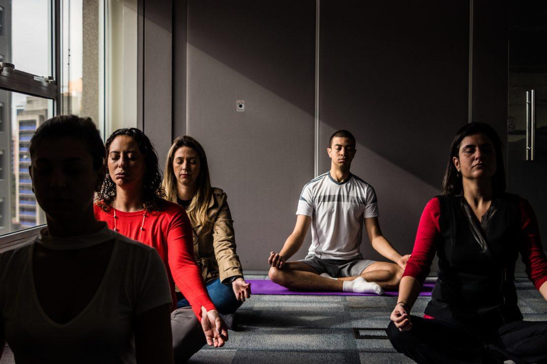 Pessoas em roupas confortáveis sentam de perna de índio e fazem meditação. Uma janela na lateral esquerda deixa um raio de luz entrar.