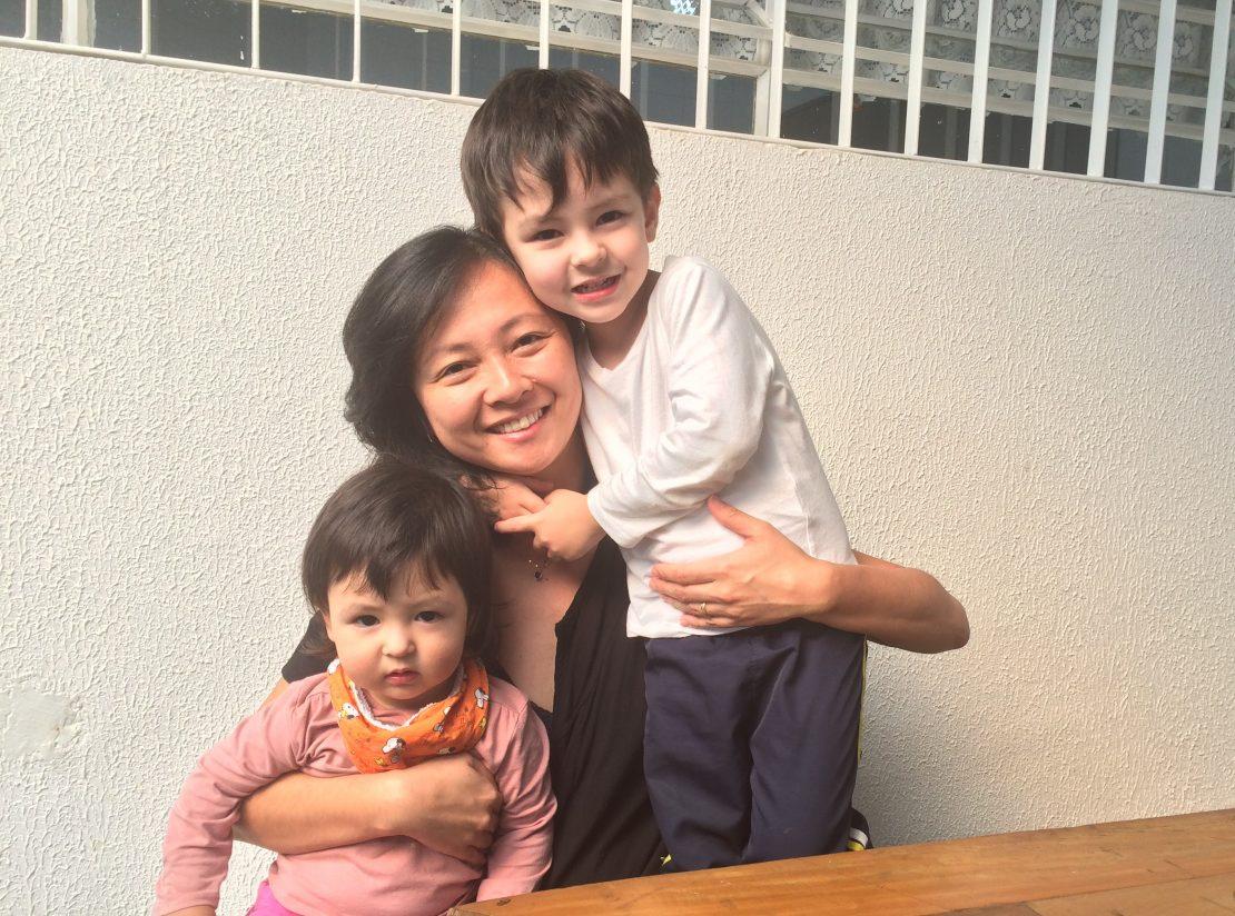 Mãe abraçada com filho e filha
